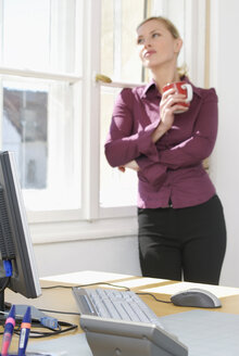 Woman in office leaning on window, close-up - VRF00042