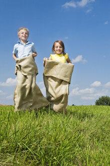 Boy and girl sack racing - LDF00533