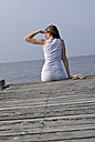 Italy, Lake Garda, Young woman (20-25) sitting on dock, rear view, close-up - DKF00116