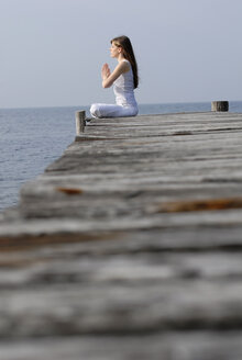 Italy, Lake Garda, Woman (20-25) exercising yoga on jetty - DKF00113