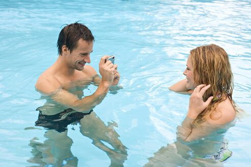 Germany, young man photographing woman in pool - BABF00332