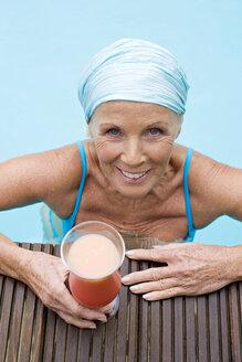 Germany, senior woman having cocktail at pool - BABF00287