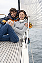 Germany, Baltic Sea, Lübecker Bucht, Young couple on sailing boat sitting and holding mugs - BAB00403