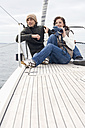 Germany, Baltic Sea, Lübecker Bucht, Young couple on boat, woman holding binoculars - BAB00397