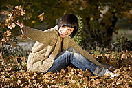 Germany, Bavaria, Young woman throwing autumn leaves, portrait - MAEF00671