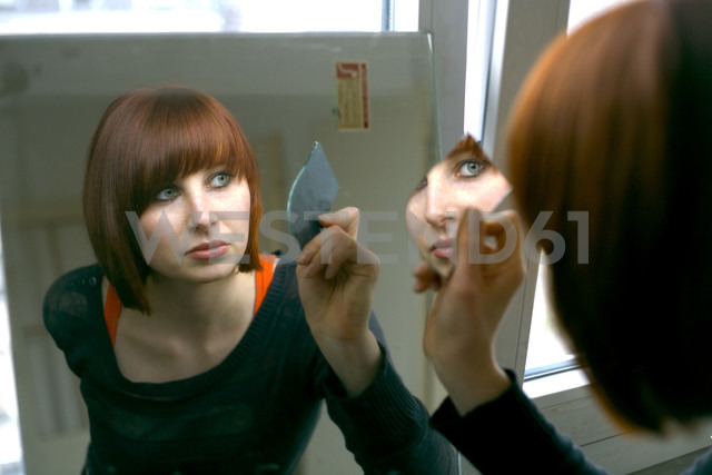 Woman looking into mirror, portrait - MFF00349