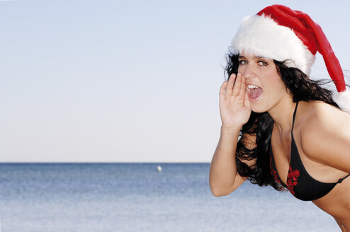 Young woman on beach, wearing Santa hat - 00344LR-U