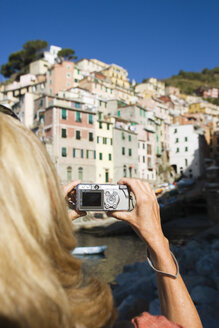 Italy, Liguria, Riomaggiore, Woman photographing houses - MRF01026