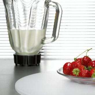 Strawberries on plate in front of mixer, close-up - CHKF00469