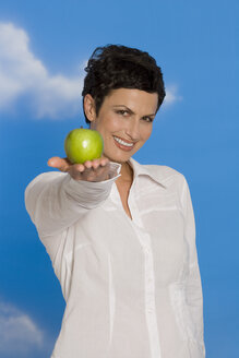 Young woman holding apple, smiling, portrait - RRF00095