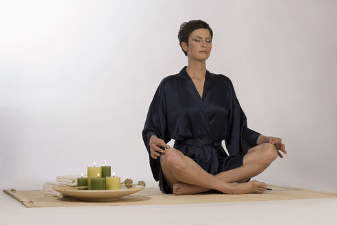 Woman meditating on yoga mat - RRF00038