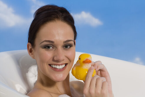 Young woman in bath holding rubber Duck, portrait - RRF00020