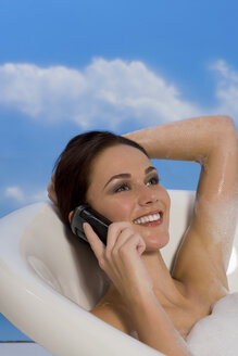 Young woman taking bubble bath and talking on mobile phone - RRF00005