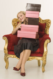 Young woman with stack of shoeboxes, portrait - WESTF07044