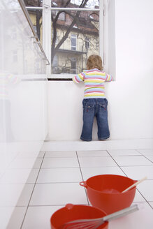Baby girl (2-3) stands at the window - SMOF00144