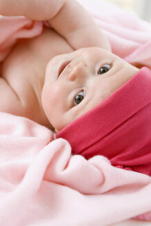 Baby girl (6-9 months) lying on back, portrait - SMOF00102