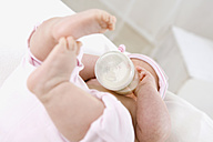 Baby girl (6-9 months) drinking milk from bottle, portrait - SMOF00099