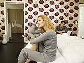 Young couple, woman sitting on edge of bed - WESTF06680