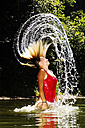 Young woman tossing her wet hair in a lake - HHF01662