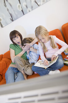 Mother and children watching television together - WESTF07358