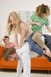 Boy (6-7) and girl (8-9) on father's back in living room - WESTF07344