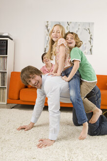 Boy (6-7) and girl (8-9) on father's back in living room - WESTF07341