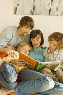 Family reading story book in living room - WESTF07277