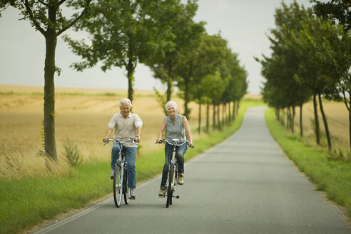 Senior couple biking on country road - WESTF07185