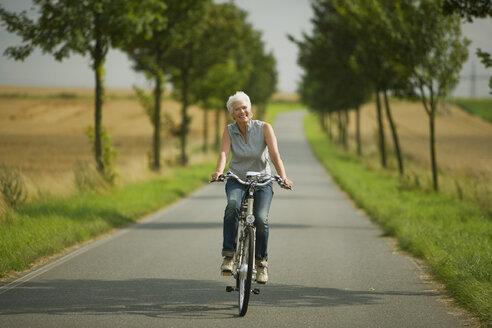 Senior woman biking on road - WESTF07181