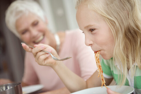 Girl (8-9) eating spaghetti, grandmother in background - HKF00209