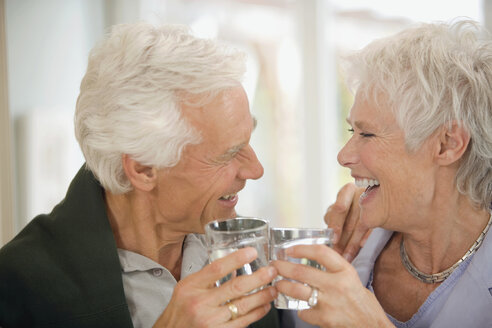 Senior couple toasting each other, smiling, portrait - HKF00185