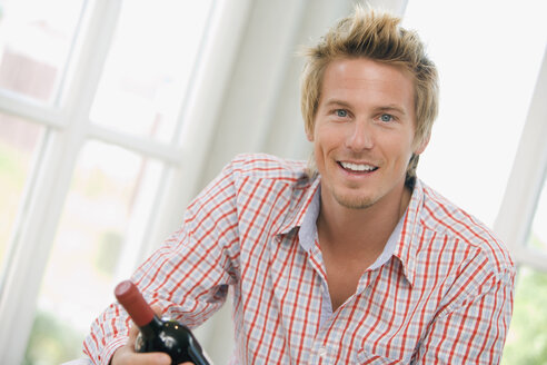 Young man holding a wine bottle, smiling, portrait - HKF00170