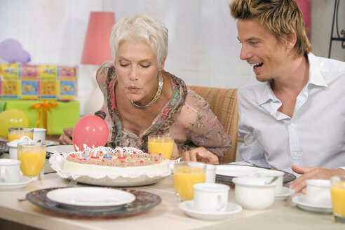 Woman blowing candle on torte, portrait - HKF00152