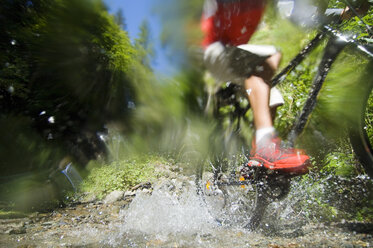 Mountainbiker crossing water, low section - HHF01918