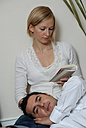 Young couple, woman reading, man's head resting on lap - DKF00163