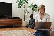 Blonde woman using laptop, portrait - DKF00160
