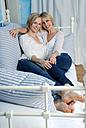 Two blonde women relaxing on bed, portrait - DKF00148