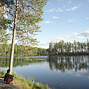 Finland, Hossa National Park, woman on lakeside - PM00528
