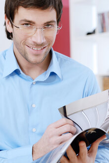 Young man holding a magazine - VRF00072