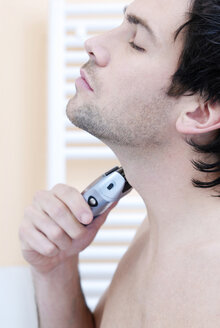 Young man using electric razor, portrait - VRF00063