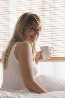 Blonde woman holding a cup of coffee, smiling, portrait - LDF00593
