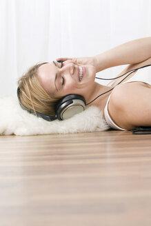 Blonde wearing headphones, smiling, portrait - LDF00572