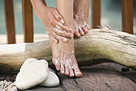 Woman applying lotion to feet, low section - ABF00194