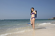 Asia, Thailand, Young woman on beach, holding fins, and diving goggles - RDF00644
