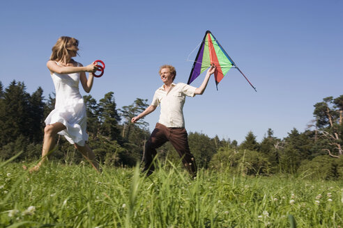 Germany, Bavaia, Young couple flying kites in meadow - RDF00590