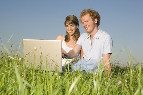 Germany, Bavaria, Young couple in meadow, using laptop, portrait - RDF00556