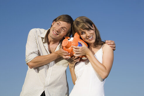 Germany, Bavaria, Young couple holding piggy bank, smiling, portrait - RDF00532