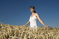 Germany, Bavaria, Young woman standing in field - RDF00521