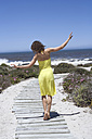 South Africa, Cape town, Young woman walking across woodway, rear view - ABF00389