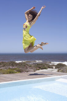 South Africa, Cape Town, Young woman jumping by swimmingpool, arms raised - ABF00383